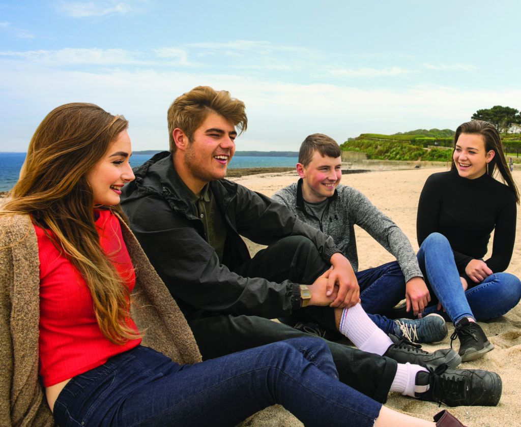 Four students, two girls and two boys approximately 18 years old sit on the sand at Gyllyngvase Beach, the ocean behind them.