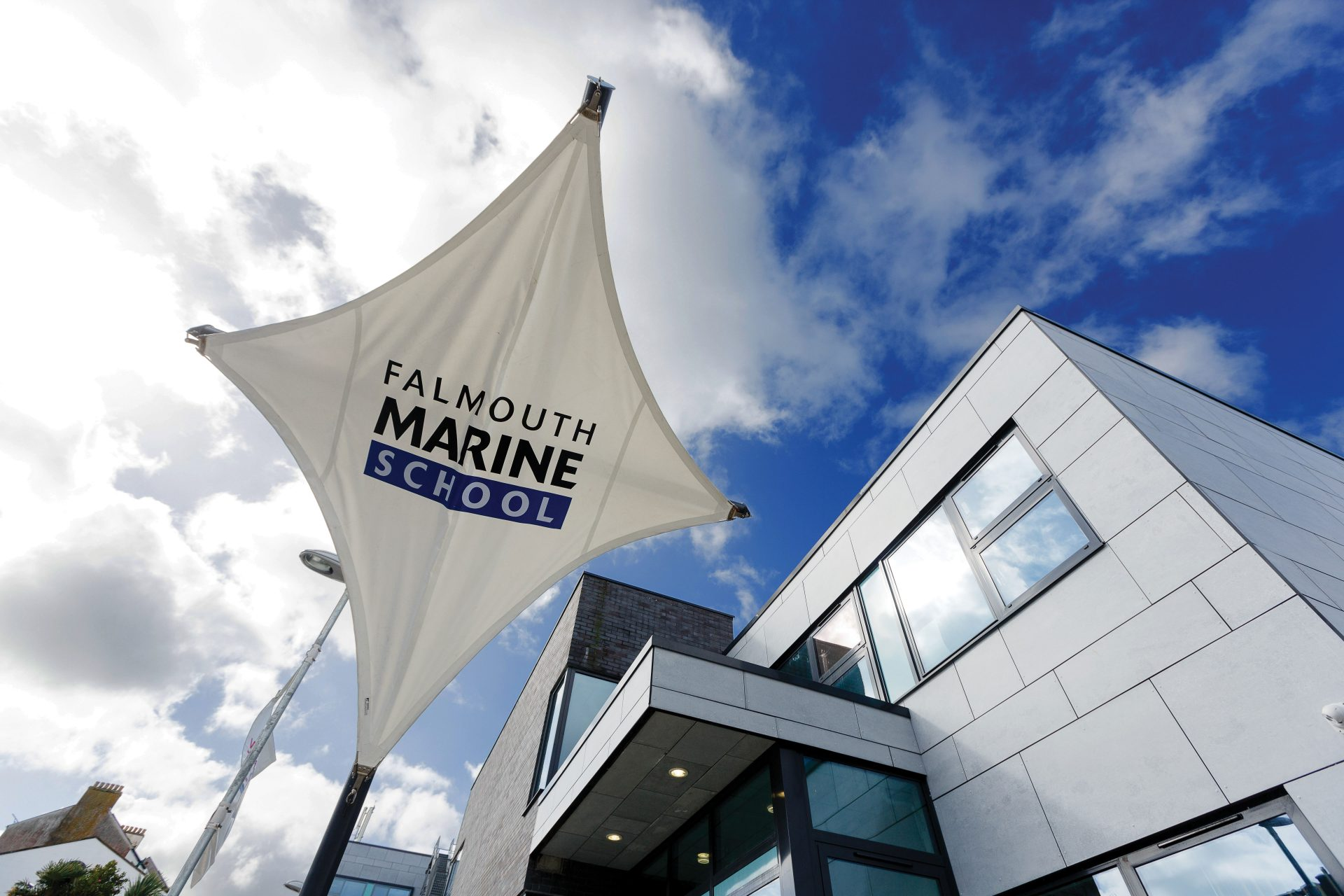 Falmouth Marine School's main entrance and logo on a sail