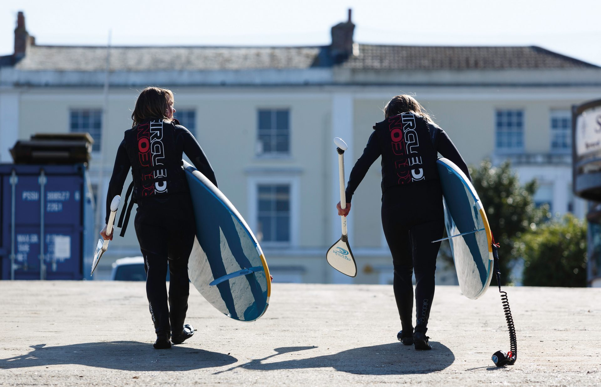 Two students walk carrying paddle boarding boards