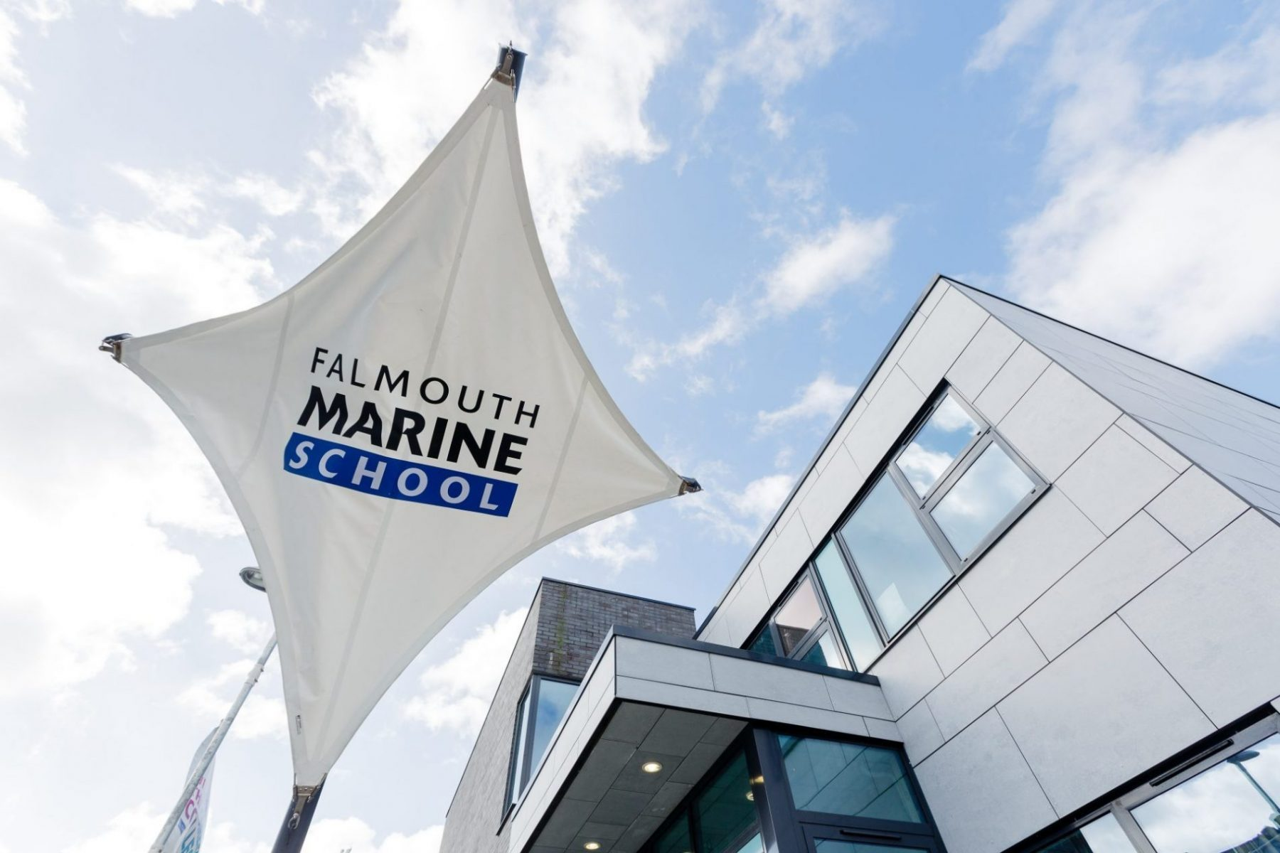 falmouth marine school flag with building and blue sky